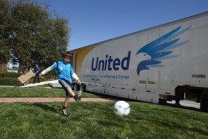 Kid in front of United Van Lines Truck